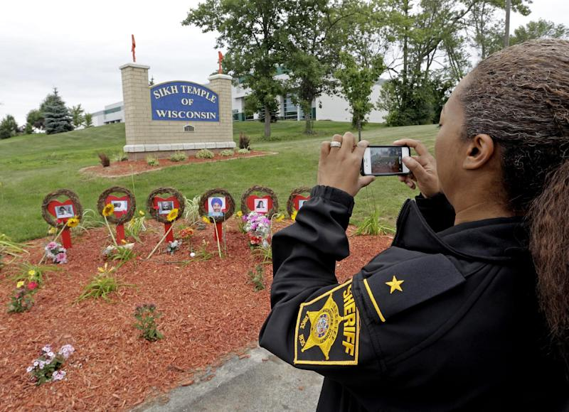Deputy Inspector Aisha Barkow takes a picture of a makeshift memorial outside the Sikh Temple of Wisconsin Monday, Aug. 5, 2013, in Oak Creek, Wis. Monday is the one-year anniversary of the shooting rampage when a white supremacist at the temple where six people were killed. (AP Photo/Morry Gash)