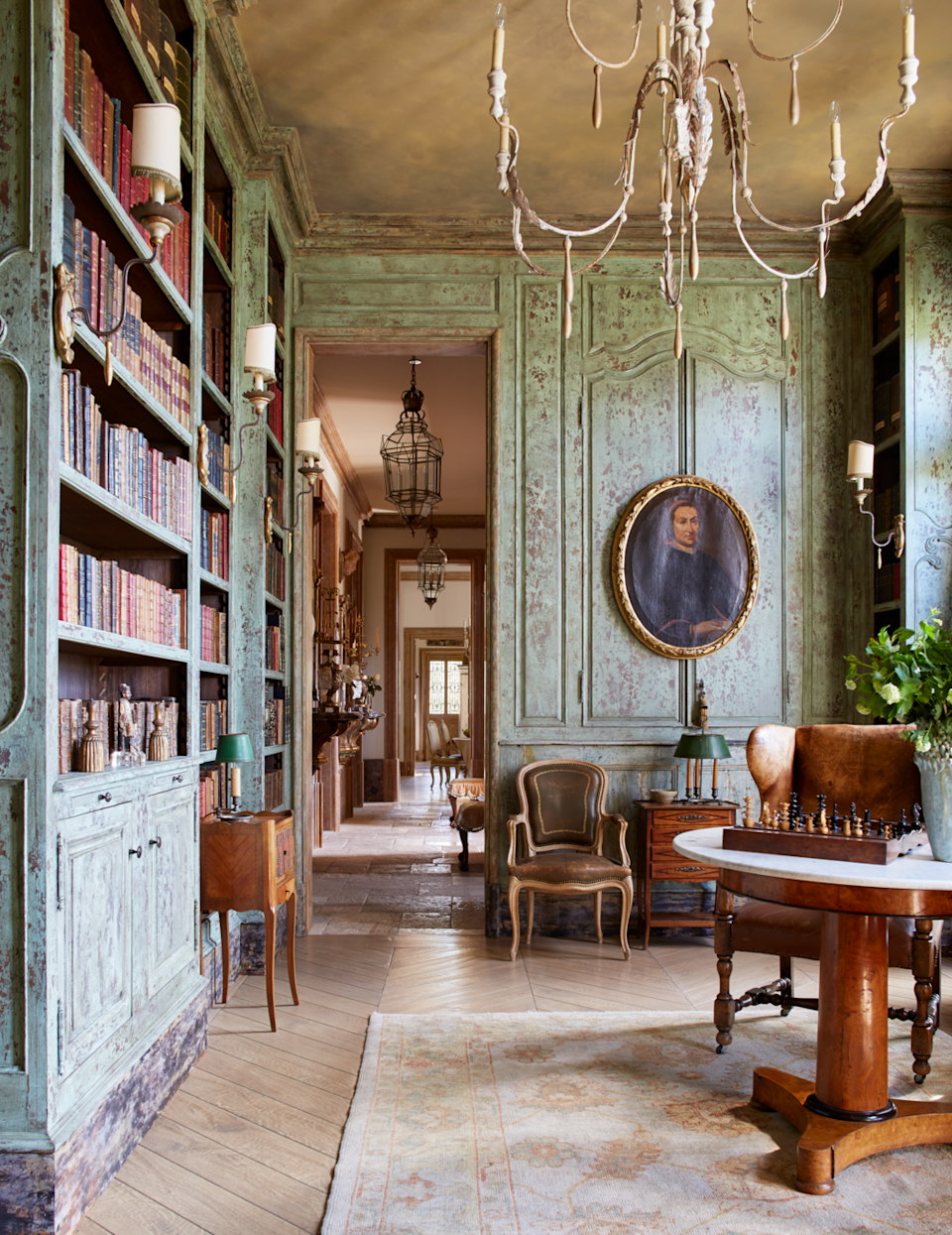 """<p>Inspired by the Villa San Michele outside of Florence, this Southern California home embraces its European influences with antiques sourced throughout the continent flooding each room. Designer <a href=""""http://www.steicheninteriordesign.com/"""" rel=""""nofollow noopener"""" target=""""_blank"""" data-ylk=""""slk:Laurie Steichen"""" class=""""link rapid-noclick-resp"""">Laurie Steichen</a> painted the paneling with an aged patina that infuses the library with a sense of history. An antique English leather wing chair is paired with a French gueridon table from <a href=""""https://www.instagram.com/brenda_antin/?hl=en"""" rel=""""nofollow noopener"""" target=""""_blank"""" data-ylk=""""slk:Brenda Antin"""" class=""""link rapid-noclick-resp"""">Brenda Antin</a>.</p>"""