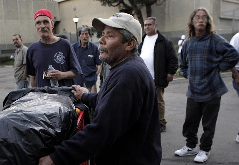 FILE- This file photo from Thursday, Jan. 5, 2012, shows homeless individuals waiting to receieve hygiene kits in Santa Ana, Calif. (AP Photo/Jae C. Hong, File)