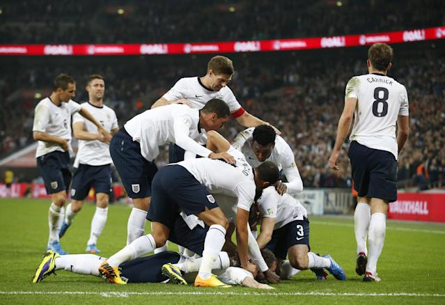 England's Wayne Rooney, on the ground, celebrates with teammates after scoring the opening goal during the World Cup Group H qualification soccer match between England and Poland at Wembley stadium in London, Tuesday, Oct. 15, 2013. (AP Photo/Matt Dunham)