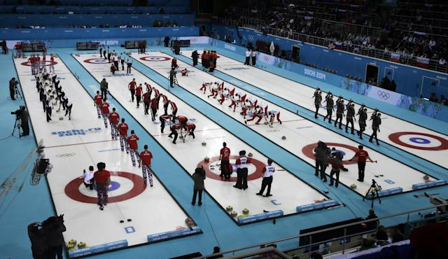 This multiple expose shows men's curling teams competing during round robin matches at the 2014 Winter Olympics, Monday, Feb. 17, 2014, in Sochi, Russia. (AP Photo/Morry Gash)