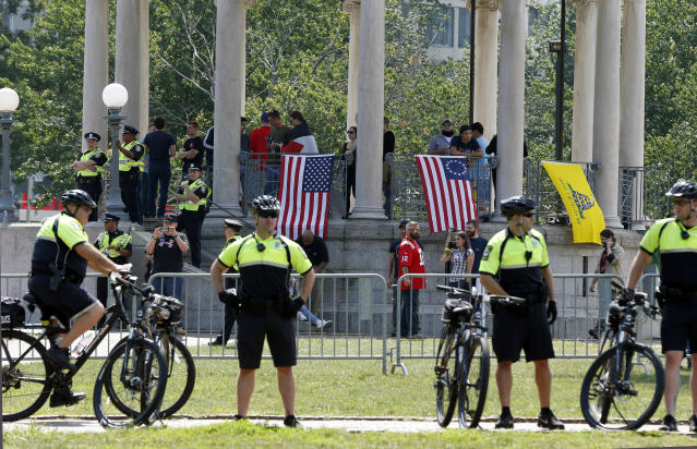 """Police stand at a barricade around the bandstand before a planned """"Free Speech"""" rally by conservative activists on Boston Common, Saturday, Aug. 19, 2017, in Boston. Police Commissioner William Evans said Friday that 500 officers, some in uniform, others undercover, would be deployed to keep the two groups apart. (AP Photo/Michael Dwyer)"""