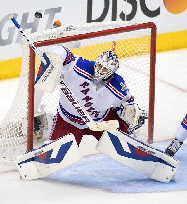 New York Rangers goalie Henrik Lundqvist, of Sweden, top, blocks by the Los Angeles Kings during the third period in Game 1 of the NHL hockey Stanley Cup Finals, Wednesday, June 4, 2014, in Los Angeles. (AP Photo/Mark J. Terrill)