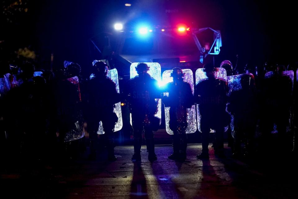 CORRECTS TO JOHN CHISHOLM NOT JOHN CHISOLM - Police line up in riot gear Friday, Oct. 9, 2020, in Wauwatosa, Wis. On Wednesday, District Attorney John Chisholm refused to issue charges against Wauwatosa Police Officer Joseph Mensah for the Feb. 2 fatal shooting of 17-year-old Alvin Cole at Mayfair Mall. (AP Photo/Morry Gash)