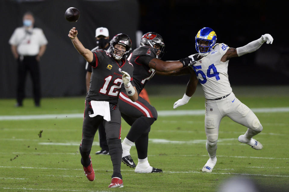 Tampa Bay Buccaneers quarterback Tom Brady (12) throws a pass as offensive tackle Tristan Wirfs (78) blocks Los Angeles Rams outside linebacker Leonard Floyd (54). (AP Photo/Jason Behnken)