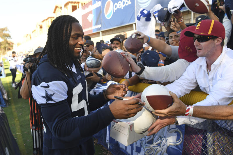 Dallas Cowboys linebacker Jaylon Smith, left, gives autographs to fans at the team's training camp in Oxnard, Calif. last year. (AP Photo/Michael Owen Baker)