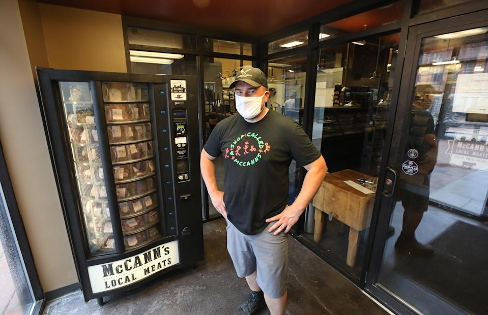Kevin McCann stands with the new meat vending machine in the lobby of McCann's Local Meats, a butcher shop on South Clinton Avenue.