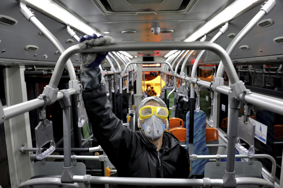 A worker disinfects a public bus against coronavirus in Tehran, Iran, in early morning of Wednesday, Feb. 26, 2020. Iran's government said Tuesday that more than a dozen people had died nationwide from the new coronavirus, rejecting claims of a much higher death toll of 50 by a lawmaker from the city of Qom that has been at the epicenter of the virus in the country. (AP Photo/Ebrahim Noroozi)