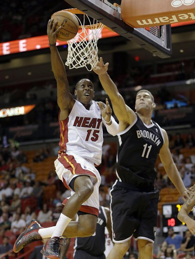 Miami Heat point guard Mario Chalmers (15) goes to the basket against Brooklyn Nets center Brook Lopez (11) in the first period of an NBA preseason basketball game, Friday, Oct. 25, 2013, in Miami. (AP Photo/Alan Diaz)