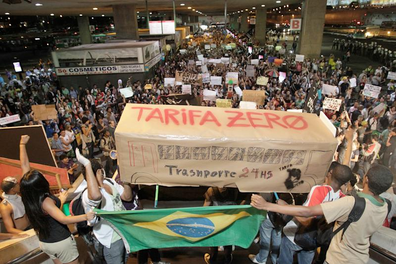 "FILE - In this June 19, 2013 file photo, Brazilians hold a poster shaped as a bus that reads in Portuguese; ""Zero fares, transport 24 hours,"" during a march demanding free public transit and against the money poured into stadiums for hosting the current Confederations Cup and next year's World Cup, at the Bus Station, in Brasilia, Brazil. The Free Fare Movement, which advocates for the elimination of all transit fees, didn't expect to become the focal point of what some Brazilian media are calling the most important mass demonstrations in the nation's history. (AP Photo/Eraldo Peres, File)"