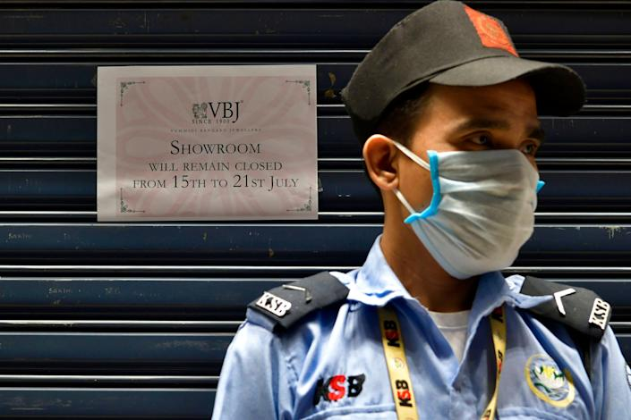 A security guard stands outside a closed jewelry store next to a sign informing customers of a weeklong closure as Bengaluru undergoes a lockdown to contain the surge of coronavirus cases, July 14, 2020. (Photo: MANJUNATH KIRAN via Getty Images)