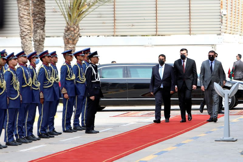 Libya's Prime Minister Abdulhamid Dbeibeh, Libya's internationally recognized former Prime Minister Fayez al-Sarraj, and Mohammed al-Menfi, Head of the Presidency Council, arrive ahead of the handover ceremony in Tripoli
