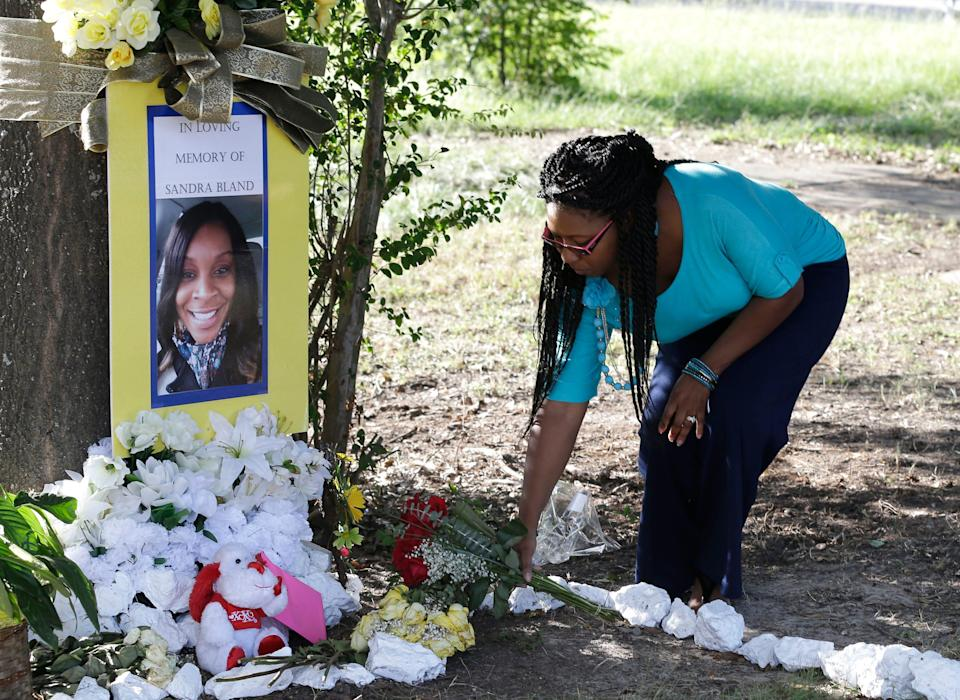 Jeanette Williams places a bouquet of roses at a memorial for Sandra Bland near Prairie View A&M University, in Prairie View, Texas on July 21, 2015.