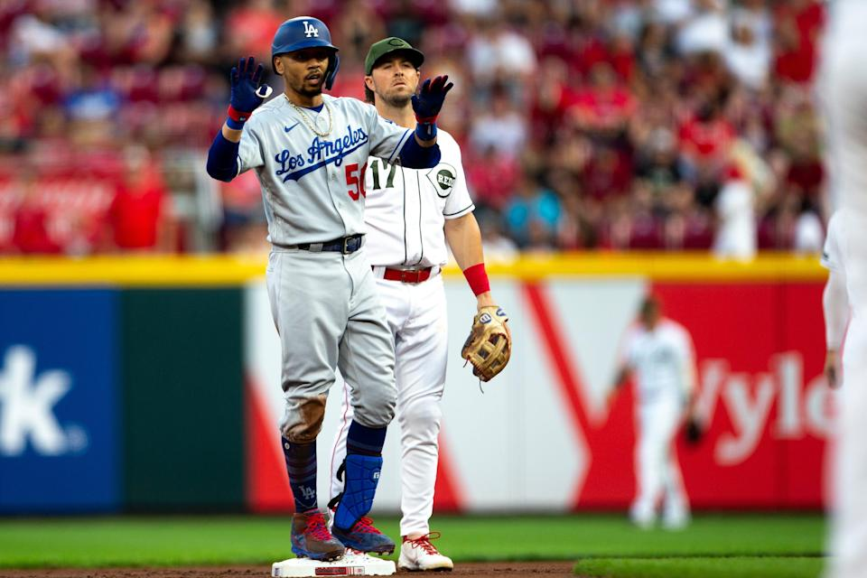 Los Angeles Dodgers right fielder Mookie Betts (50) celebrates as Cincinnati Reds shortstop Kyle Farmer (17) looks on after hitting a double in the first inning of the MLB baseball game between Cincinnati Reds and Los Angeles Dodgers on Friday, Sept. 17, 2021, at Great American Ball Park in Cincinnati.