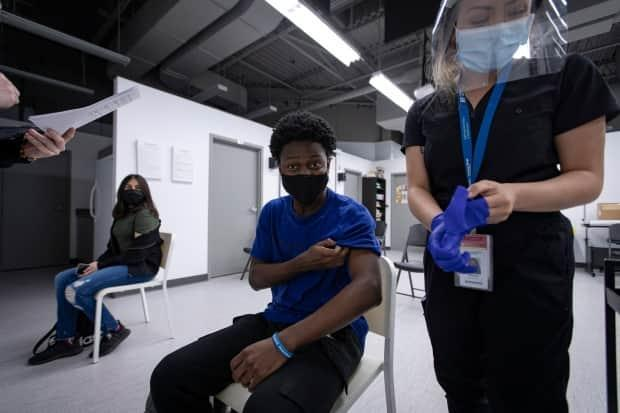 Black Creek Community Health volunteer Rayvon Johnson, 18, gets his first dose of the Moderna COVID-19 vaccine in Toronto on Apr. 14, 2021.