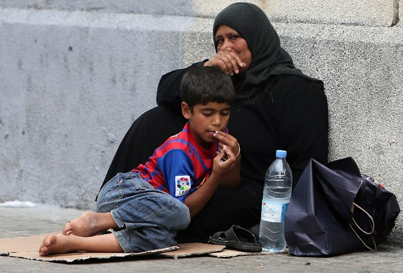 A Syrian refugee boy sits with his mother as they beg on the sidewalk in Beirut on September 18, 2013 (AFP Photo/Joseph Eid)