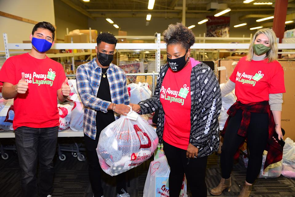 Mo Adams of Atlanta United FC (second from left) appeared at a drive-through event at an Atlanta Burlington Coat Factory, where he cleared $12,000 worth of layaway balances. (Photo: Pay Away the Layway)