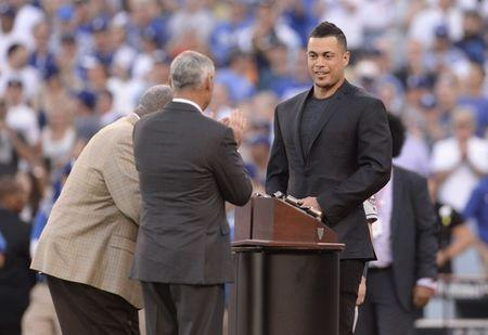 FILE PHOTO: Oct 25, 2017; Los Angeles, CA, USA; Miami Marlins outfielder Giancarlo Stanton is greeted by MLB commissioner Rob Manfred and Hank Aaron before game two of the 2017 World Series between the Los Angeles Dodgers and the Houston Astros at Dodger Stadium. Gary A. Vasquez-USA TODAY Sports