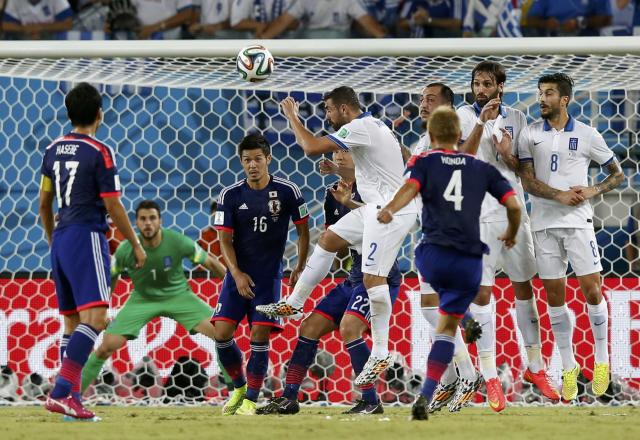 Japan's Keisuke Honda (4) fails to score during their 2014 World Cup Group C soccer match against Greece at the Dunas arena in Natal June 19, 2014. REUTERS/Toru Hanai (BRAZIL - Tags: SOCCER SPORT WORLD CUP)