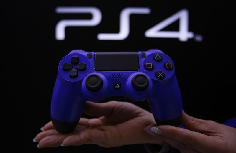 A staff at the PlayStation 4 launch event poses with the PlayStation 4's game controller before its domestic launch event at the Sony Showroom in Tokyo February 21, 2014 file photo. REUTERS/Yuya Shino