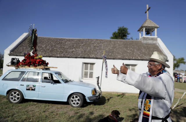 Father Roy Snipes gives the thumbs-up sign to a supporter after he lead a procession to the La Lomita Chapel along a levee toward the Rio Grande to oppose the wall the U.S. government wants to build on the river separating Texas and Mexico, Saturday, Aug. 12, 2017, in Mission, Texas. The area would be the target of new barrier construction under the Trump administration's current plan. (AP Photo/Eric Gay)