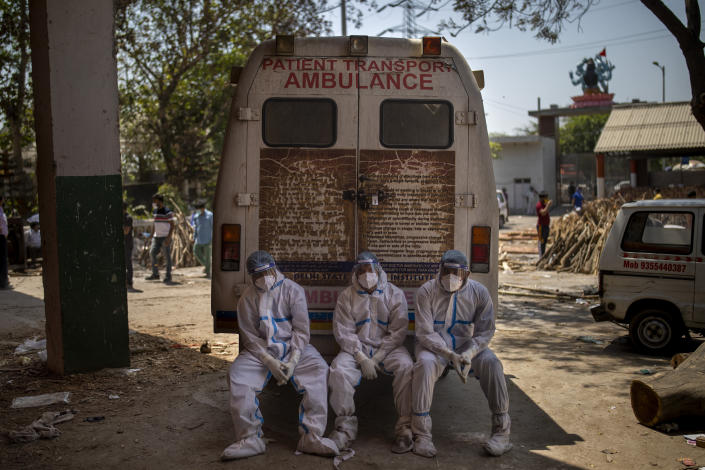 Exhausted workers, who bring dead bodies for cremation, sit on the rear step of an ambulance inside a crematorium, in New Delhi, India, Saturday, April 24, 2021. Delhi has been cremating so many bodies of coronavirus victims that authorities are getting requests to start cutting down trees in city parks, as a second record surge has brought India's tattered healthcare system to its knees. (AP Photo/Altaf Qadri)