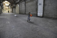Arman, 2, plays in front of closed shops of Tehran's Grand Bazaar, Iran, Saturday, April 10, 2021. Iran on Saturday imposed partial lockdown on businesses in major shopping centers as well as intercity travels through personal cars in major cities including capital Tehran as it struggles with the worst outbreak of the coronavirus in the Mideast region. (AP Photo/Vahid Salemi)