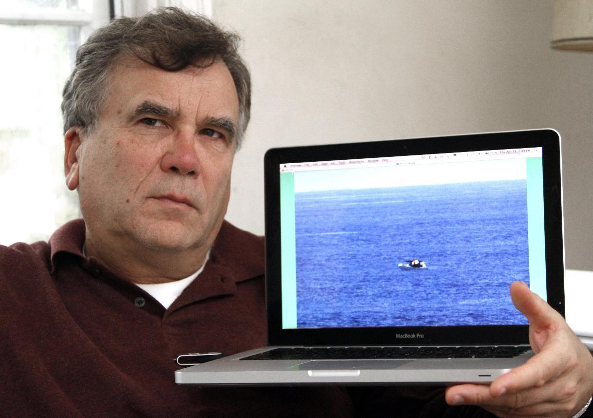 Jeff Gilligan, who was a passenger on the American-based cruise ship Star Princess last March, holds a laptop in Portland, Ore., Thursday, April 19, 2012, with the photo he took of a fishing vessel adrift in the Pacific Ocean off the Galapagos Islands while on the cruise. Gilligan and another American aboard the cruise ship, in the same area, believe they saw the fishermen adrift at sea and they alerted the crew, but the luxury liner continued on its course. Two of the three men in the fishing vessel died from exposure. The company that owns the Star Princess cruise ship says it is looking into whether the crew ignored the fishermen's signals that they needed help. (AP Photo/Jeff Gilligan)