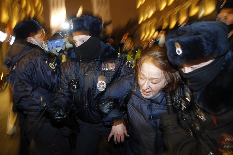 Police officers detain a Navalny supporter during a protest in St. Petersburg, Russia, Tuesday, Feb. 2, 2021. A Moscow court has ordered Russian opposition leader Alexei Navalny to prison for more than 2 1/2 years on charges that he violated the terms of his probation while he was recuperating in Germany from nerve-agent poisoning. Navalny, who is the most prominent critic of President Vladimir Putin, had earlier denounced the proceedings as a vain attempt by the Kremlin to scare millions of Russians into submission. (AP Photo/Dmitri Lovetsky)