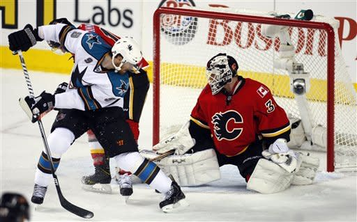 San Jose Sharks' Martin Havlat, left, of the Czech Republic, tries to score on a backhand shot between his legs as Calgary Flames goalie Miikka Kiprusoff, of Finland, makes the stop during the first period of an NHL hockey game, Sunday, Jan. 20, 2013, in Calgary, Alberta. (AP Photo/The Canadian Press, Jeff McIntosh)
