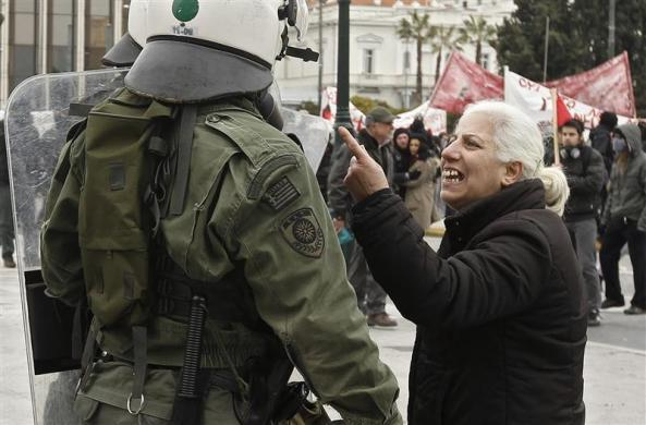 A demonstrator confronts riot police during protests against planned reforms by Greece's coalition government in Athens, February 10, 2012.