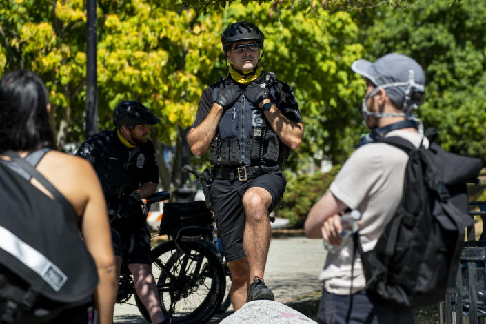 Seattle police officers stand in front of protesters on Aug. 14 after police conducted a sweep of Cal Anderson Park in the area formerly known as CHOP. (David Ryder/Getty Images)