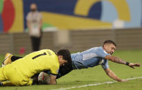 Bolivia's goalkeeper Carlos Lampe, left, stops an attempt on goal by Uruguay's Giorgian de Arrascaeta during a Copa America soccer match at Arena Pantanal in Cuiaba, Brazil, Thursday, June 24, 2021. (AP Photo/Andre Penner)