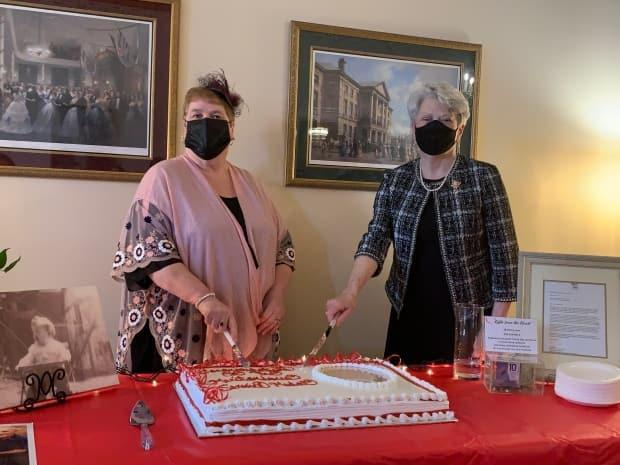 Lt.-Gov. Antoinette Perry, right, helped Begg-Brooks cut the cake for her 75th birthday.