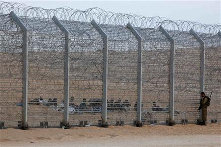 File photo of an Israeli soldier and African migrants on two sides of border fence with Egypt in southern Israel