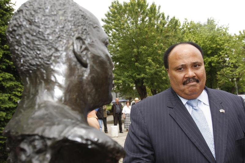 """FILE - In this Wednesday, May 13, 2009 file photo, Martin Luther King III visits the statue of his father the Rev. Dr. Martin Luther King Jr., during his visit to the Bosnian town of Tuzla, 72 kilometers (45 miles) north of Bosnian capital of Sarajevo. King arrived in a five-day visit to Bosnia during which he is scheduled to hold several lectures and visit different locations promoting activities of the """"Realizing Dreams"""" organization over which he presides. (AP Photo/Amel Emric, File)"""