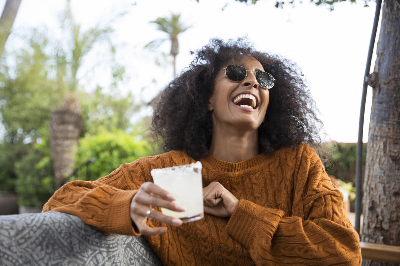 Lifestyle portrait of black woman sitting in outdoor bar with cocktail