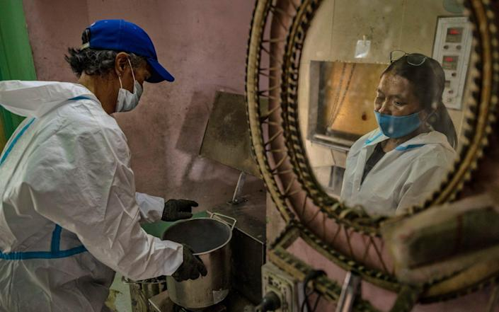 Cemetery workers grind the ashes of someone who died of Covid-19, at a public crematorium in Pasay, Metro Manila, Philippines - Ezra Acayan/Getty