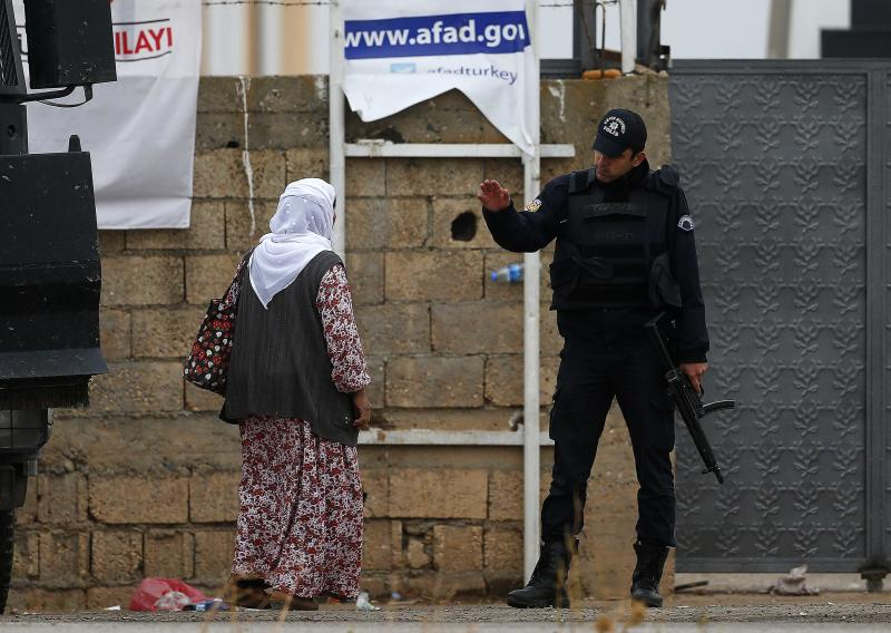 A Turkish policeman stops a Kurdish woman before she approaches the gate of a camp that hosts Peshmerga fighters in the border town of Suruc