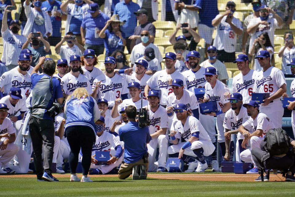 Members of the Los Angeles Dodgers pose for photos with their 2020 World Series Championship rings before a baseball game against the Washington Nationals Friday, April 9, 2021, in Los Angeles. (AP Photo/Marcio Jose Sanchez)