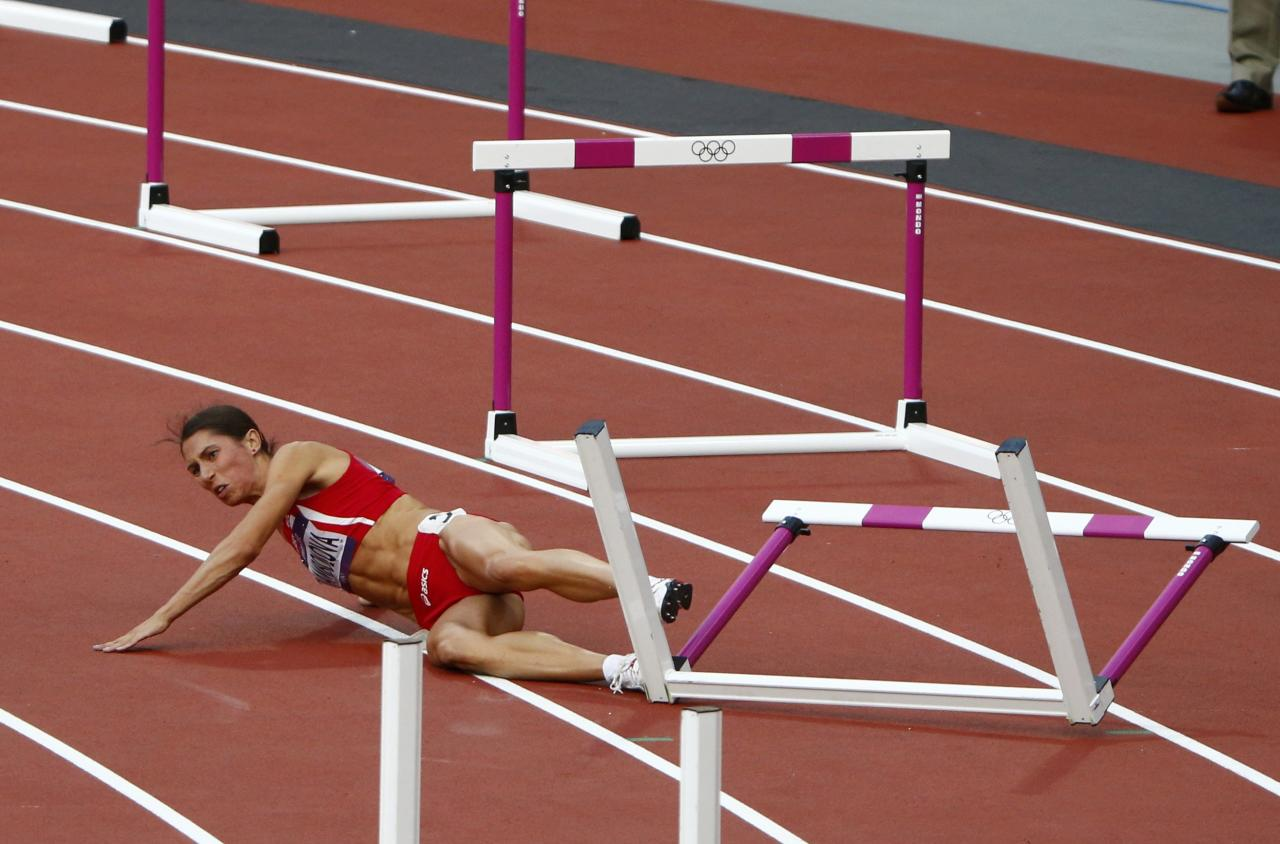 Bulgaria's Vania Stambolova crashes into a hurdle during the women's 400m hurdles round 1 heat during the London 2012 Olympic Games at the Olympic Stadium August 5, 2012. REUTERS/David Gray (BRITAIN  - Tags: OLYMPICS SPORT ATHLETICS)
