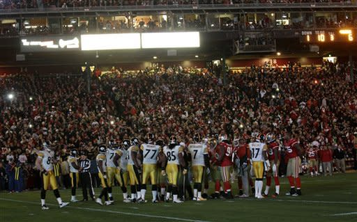 The Pittsburgh Steelers' offense and the San Francisco 49ers' defense stand on the field during a power outage during the second quarter of an NFL football game in San Francisco, Monday, Dec. 19, 2011. (AP Photo/Marcio Jose Sanchez)