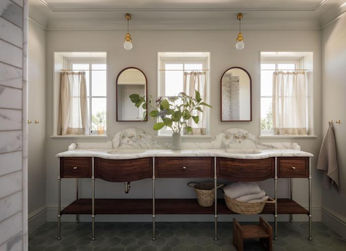 This bathroom features a marble-clad undulating double sink.