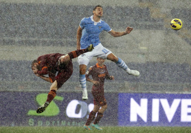 AS Roma's Daniele De Rossi (L) jumps for the ball with SS Lazio's Miroslav Klose during their Italian Serie A soccer match at the Olympic stadium in Rome November 11, 2012. Lazio won 3-2. REUTERS/Alessandro Bianchi (ITALY - Tags: SPORT SOCCER)