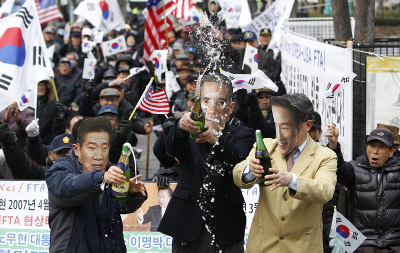 South Korean activists wearing masks of U.S. President Barack Obama, center, South Korean President Lee Myung-bak, right, and former President late Roh Moo-hyun, open bottles of champagne to celebrate the free trade agreement, or FTA, with the United States during a rally near the U.S. Embassy in Seoul, South Korea, Wednesday, March 14, 2012.  South Korea is implementing its long-stalled free trade deal with the United States about five years after the two countries struck the accord.  South Korean trade officials say the pact aimed at slashing tariffs and other trade barriers is to take effect at midnight Wednesday.  (AP Photo/Lee Jin-man)