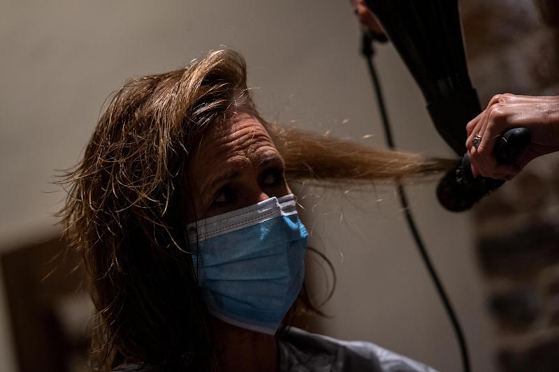 A woman gets her hair cut while wearing a mask in Canterbury (Getty Images)