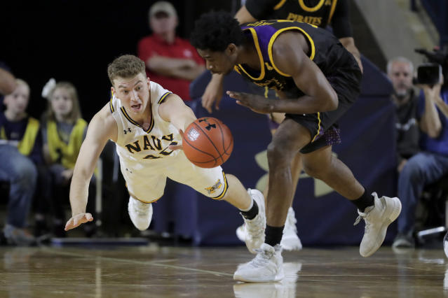Navy center Evan Wieck, left, dives for the ball while competing for possession with East Carolina guard Bitumba Baruti during the first half of an NCAA college basketball game at the Veterans Classic Tournament, Friday, Nov. 8, 2019, in Annapolis, Md. (AP Photo/Julio Cortez)
