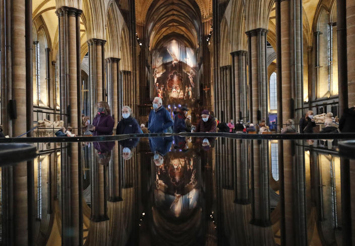 People are reflected in the 'Refection Pool' inside Salisbury Cathedral in Salisbury, England, Wednesday, Jan. 20, 2021, as they leave after receiving their Pfizer-BioNTech vaccination. Salisbury Cathedral opened its doors for the second time as a venue for the Sarum South Primary Care Network COVID-19 Local Vaccination Service. (AP Photo/Frank Augstein)