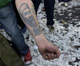 A man shows his arm tatooed with a portrait of Osama Bin Laden and an airplane before crashing into the World Trade Center during a march in Buenos Aires in 2016 against the government's cuts in public expenditure and jobs