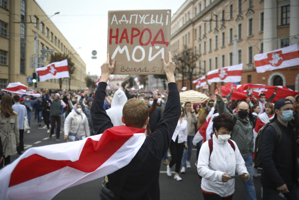 """A man holds placard reading """"Let my people go"""" during an opposition rally to protest the official presidential election results in Minsk, Belarus, Sunday, Sept. 27, 2020. Hundreds of thousands of Belarusians have been protesting daily since the Aug. 9 presidential election. (AP Photo/TUT.by)"""